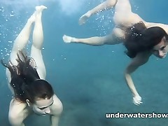 Julia and Masha are swimming in nature's garb in the sea